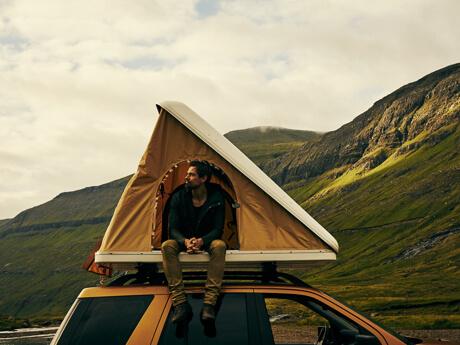 Mann in Zelt auf Autodach